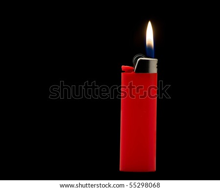 Lit red lighter isolated on black background