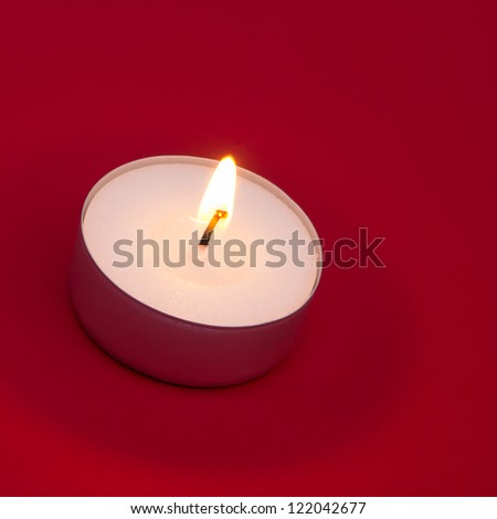 Lit tea light on red background with copy space
