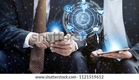 Litcoin and cryptocurrency investing concept - Businessman using mobile phone application to trade Litcoin LTC with another trader in modern graphic interface. Blockchain and financial technology. #1121519612