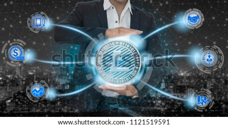 Litecoin and cryptocurrency investing concept - Businessman holding Litecoin (LTC) with mobile application business icons showing exchanging, trading, transfer and investment of blockchain technology.