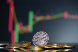 Litecoin coin LTC cryptocurrency group symbol and stock chart candlestick up trend win stock defocused background on business computer Use technology crypto currencies blockchain close up coin.