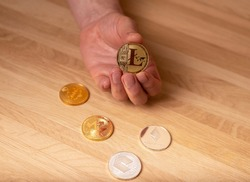 Litecoin golden coin in male hand vs other crypto currency. LTC payments.