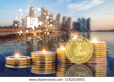 Litecoin LTC and cryptocurrency investing concept - Physical Litecoin coins with city background and exchange market trading price chart. Blockchain and financial technology.