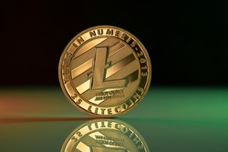 Litecoin LTC cryptocurrency physical coin placed on reflective surface and lit with green and red lights