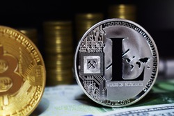 Litecoin LTC is surrounded by a money background. Concept of cryptocurrency.