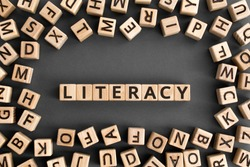 literacy - word from wooden blocks with letters, basic skill or knowledge literacy concept, random letters around, top view on wooden background