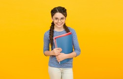 Literature and creativity. Happy kid study literature at school. Little girl hold books yellow background.