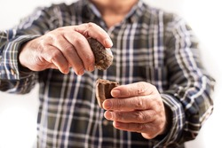 Lithic art. The hands of a man shows the procedure that was used in the stone age to make tools. In one hand a round hammer and in the other the Paleolithic bifacial tool. Percussion. Evolution. Age