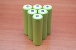 Lithium Ion cells, type 18650 with standard positive pole. A typical battery that powers majority of electric vehicles and consumer devices. Brown background