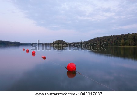 Photo of  Lithuanian National Park in Moletai region Asveja lake, red buoys on lake water at sunset.