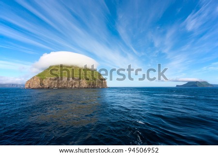 Litla Dimun, Faroe Islands. Small green island covered by lenticular clouds. - stock photo