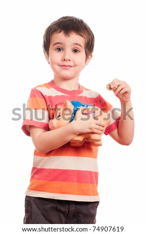 Litle boy puts the coin into the piggy bank isolated on white