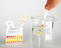 Litmus strips for measurement of acidity. Beaker with water. Water tester. PH test.