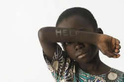 Littel African boy asks for help by covering his face with his a