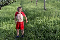 Little a boy with his shirt raised shows his stomach and standing on a meadow in nature on a sunny spring day