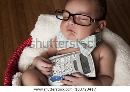 Little Accountant.  Adorable newborn wearing glasses and a bow-tie and holding a calculator.