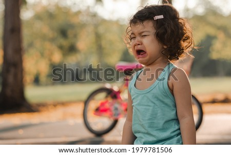 Little adorable angry caucasian curly hair girl standing outdoor in garden in summer holiday at evening, crying with sadness, depression of hurt and pain with copy space. Education and Kid Concept Photo stock ©