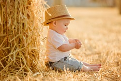 Little adorable baby boy with big brown eyes in a hat sits in a field near haystacks at sunset summer portrait in profile