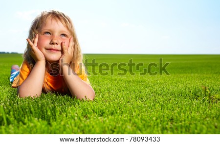 Little adorable girl lying on grass