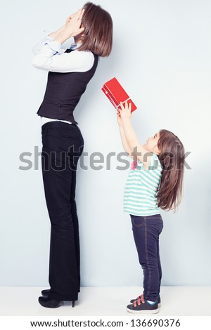 little adorable girl making a surprise for her mom on blue background - stock photo