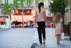 Little adorable girl with mother on shopping in Paris outdoors