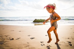 little adorable girl 2-3 years plays joyfully on the beach in sunset  on holiday