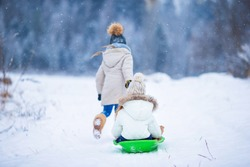 Little adorable girls enjoy a sleigh ride. Child sledding. Children play outdoors in snow. Family vacation on Christmas eve outdoors