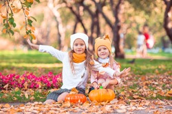 Little adorable girls with pumpkin outdoors on a warm autumn day. Portrait of kids in fall on october