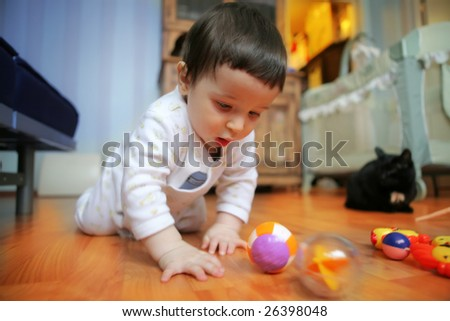 little adorable infant plays on floor in the room with furniture, soft focus