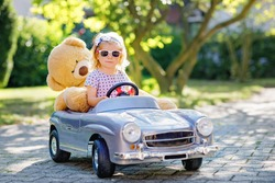 Little adorable toddler girl driving big vintage toy car and having fun with playing with plush toy bear, outdoors. Gorgeous happy healthy child enjoying warm summer day. Smiling stunning kid in gaden