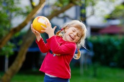 Little adorable toddler girl playing with ball outdoors. Happy smiling child catching and throwing, laughing and making sports. Active leisure with children and kids.