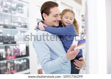 Little advisor. Cheerful adorable man holding girl and examining drug