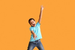 Little African-American boy dancing and singing against color background