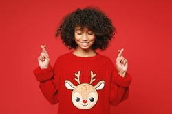 Little african american curly kid girl 13 years old in knitted cozy deer Christmas sweater keep fingers crossed isolated on bright red background children studio portrait. Childhood lifestyle concept