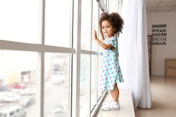 Little African-American girl near window. Child in danger