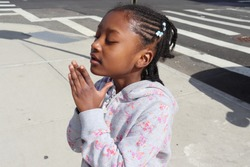 Little African American girl praying, dreaming, wishing outside on a city street.