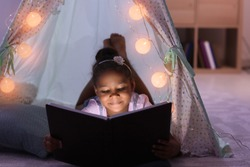 Little African-American girl reading bedtime story in hovel