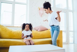 Little African American girl sitting on comfortable sofa and playing video games while irate mother standing near with palms up