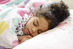 Little African American girl sleeping in bed
