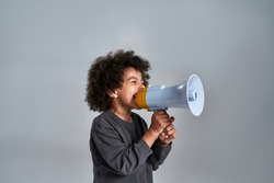 Little african american kid talking into megaphone while posing sideways to camera on light background with copy space. Stop racism concept