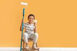 Little African-American painter against color wall