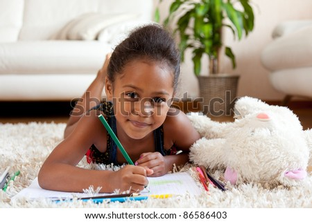 Little African Asian girl  drawing, lying down on the floor #86586403