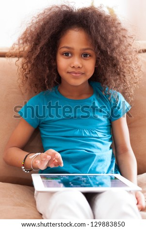 Little african asian girl seated on the couch using a tablet  pc - stock photo