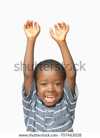 Little African boy holding his hands up in the air whilst laughing and smiling #707463028