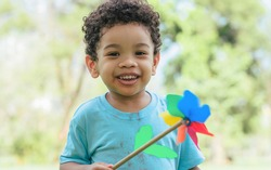 Little African curly hair boy wearing blue shirt playing and holding wind turbine toy in green field outdoor park, smiling with happiness. Education and Learning Concept