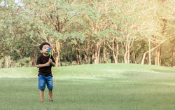 Little african curly hair boy wearing brown shirt playing and holding and blowing wind turbine toy in green field outdoor park. Education and Learning Concept