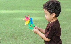 Little african curly hair boy wearing brown shirt playing and holding wind turbine toy in green field outdoor park. Education and Learning Concept