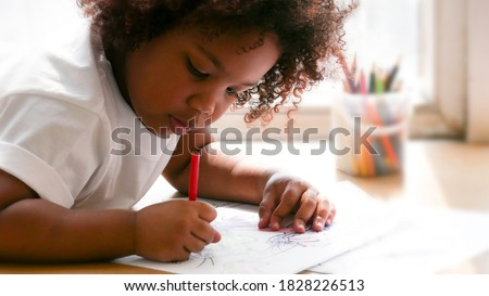 Little African girl painting and drawing on paper. Preschool girl lying writing on floor. Stock photo ©