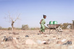 Little African Woman Transporting Fresh Water as a drought symbol