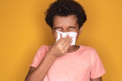 Little afro child boy blow his nose. Sick child with napkin . Allergic kid, flu season. Kid with cold rhinitis, get cold snot nose. virus and infection